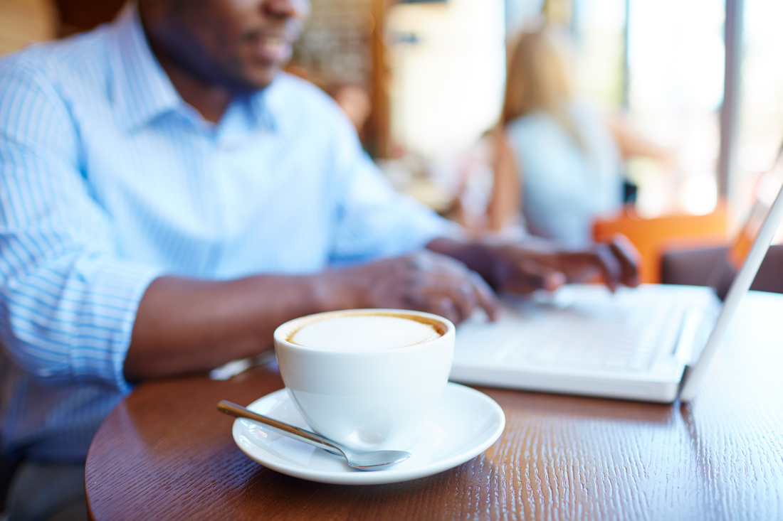 Man sitting in a cafe with a coffee and laptop